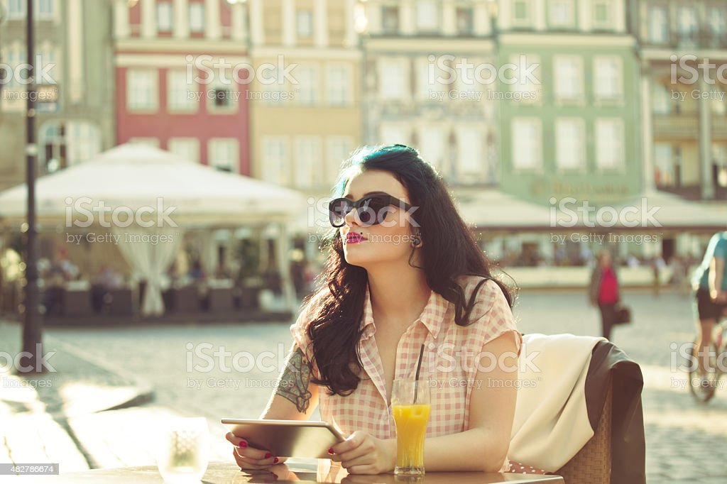 Young woman using a digital tablet in the outdoor restaurant Young hipster woman with tattoo on her arm wearing sunglasses sitting at the table in the outdoor restaurant in the city, holding a digital tablet and looking away. Orange juice on the table. Summer time.  20-24 Years Stock Photo