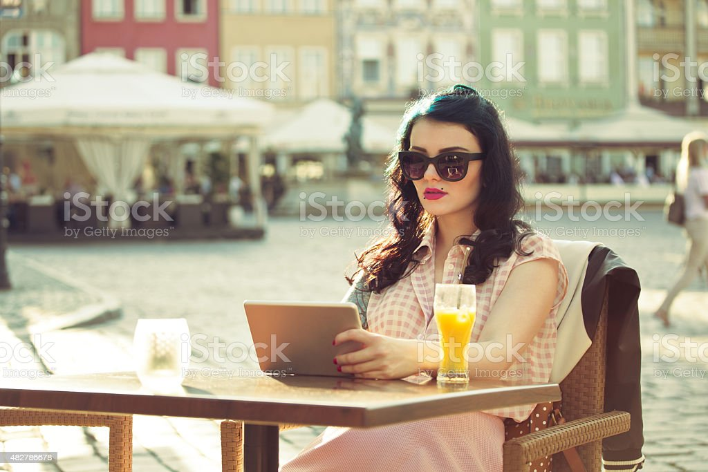 Young woman using a digital tablet in the outdoor restaurant Young hipster woman with tattoo on her arm wearing sunglasses sitting at the table in the outdoor restaurant in the city and using a digital tablet. Orange juice on the table. Summer time.  20-24 Years Stock Photo
