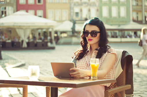 Young Woman Using A Digital Tablet In The Outdoor Restaurant Stock Photo - Download Image Now