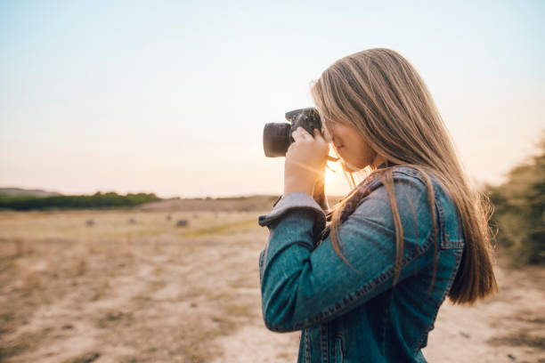 Young woman using a DSLR camera stock photo