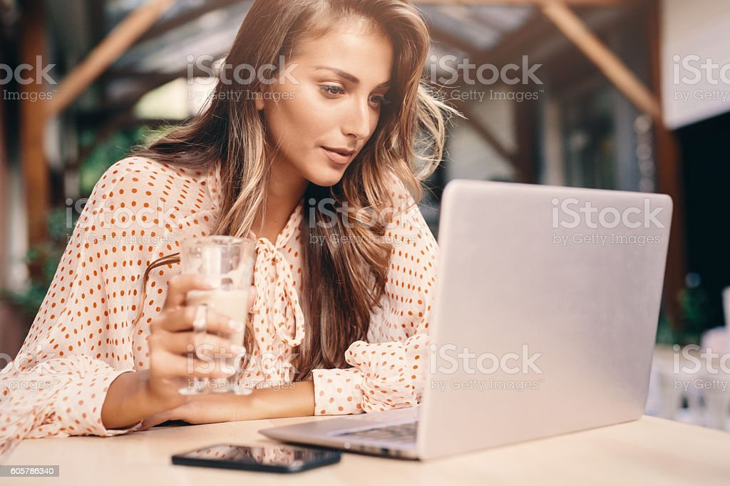 Young woman using a laptop at the cafe – Foto