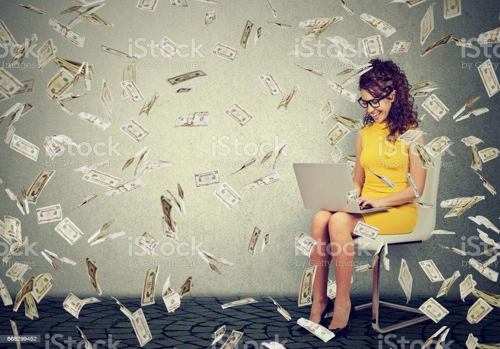 Young woman using a laptop building online business making money cash falling down - foto stock