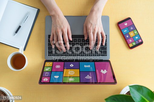 995213208 istock photo Young woman using a laptop PC and a smart phone. 1172882524