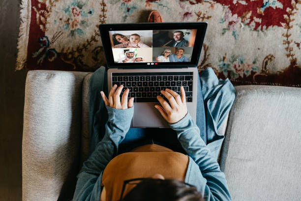 Young woman using a laptop to connect with her friends and parents during quarantine Young woman using a laptop to connect with her friends and parents during quarantine. She's having a video conference during Coronavirus COVID-19 time. quarantine stock pictures, royalty-free photos & images