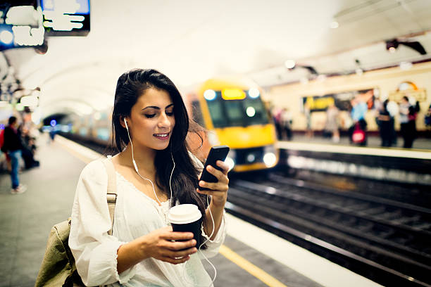 Young woman using a phone at train station in Sydney stock photo