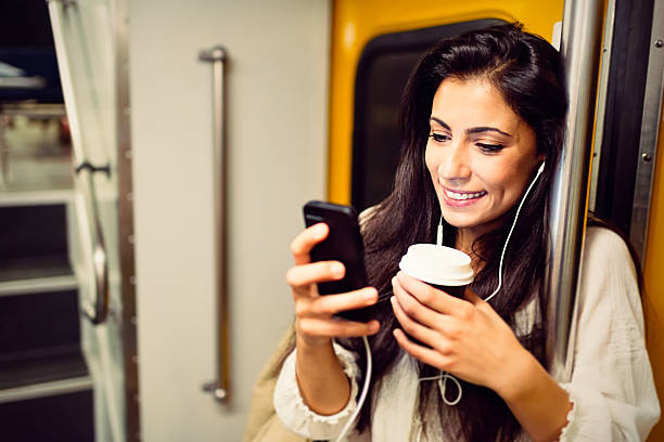 Young woman using a phone in subway train stock photo