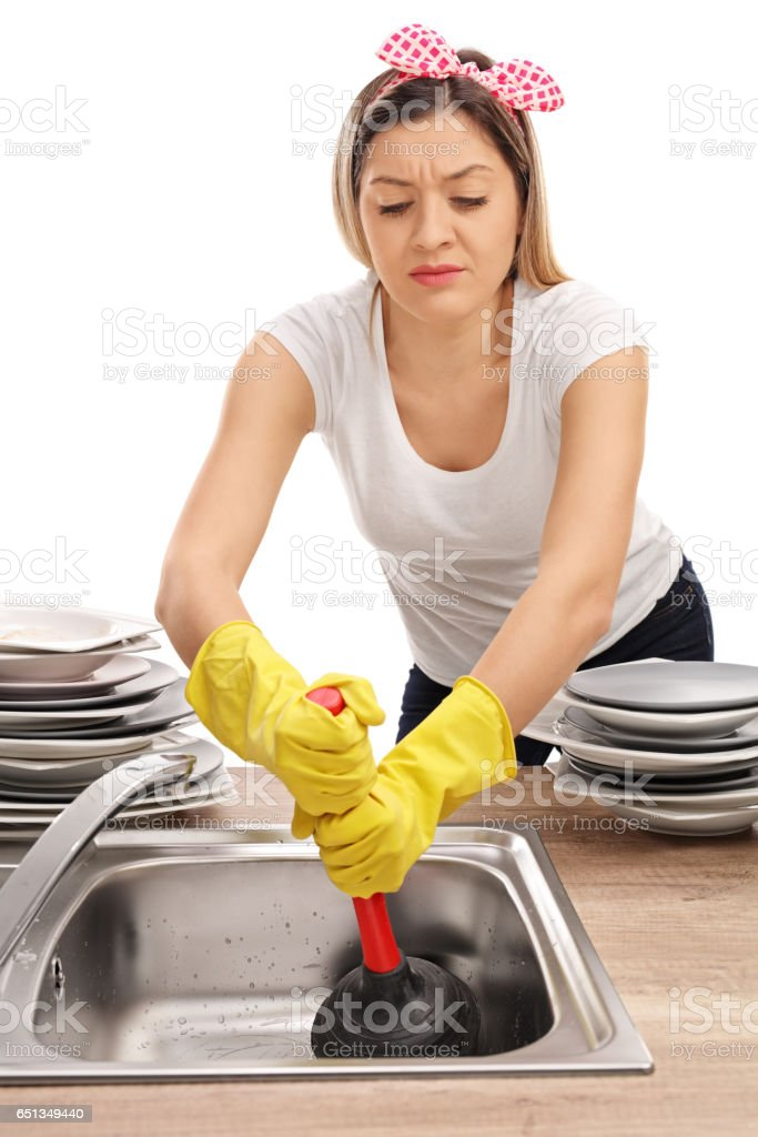 Young woman using a plunger to unclog a sink stock photo