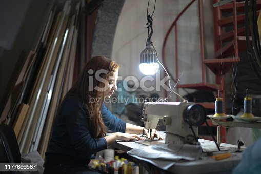 Young woman using a sewing machine in upholstery workshop
