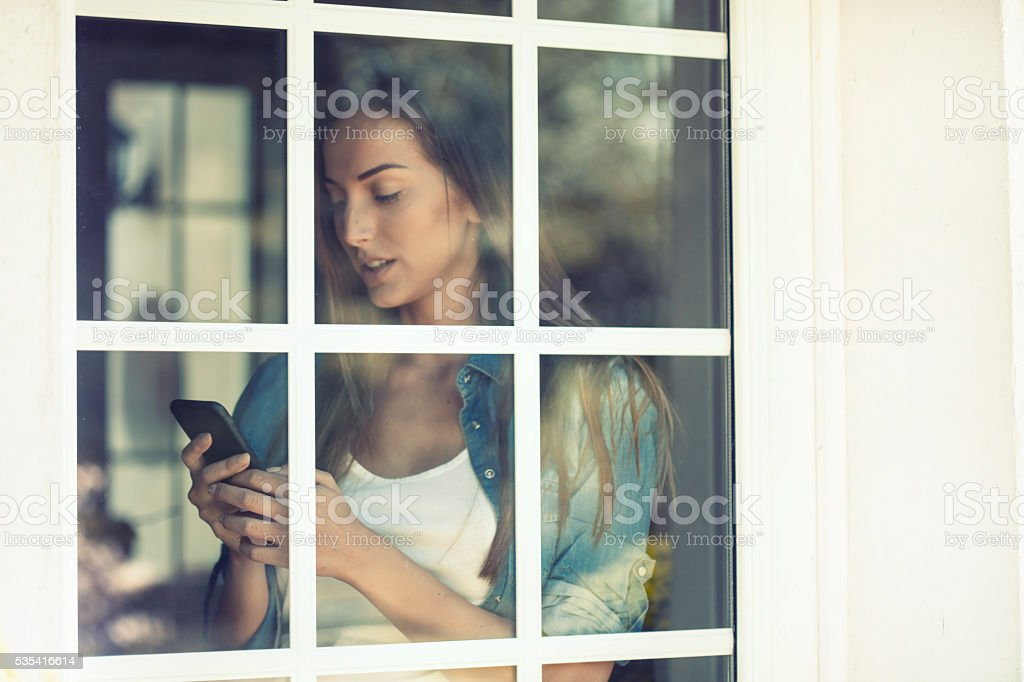 Young woman using a smart phone behind a window stock photo