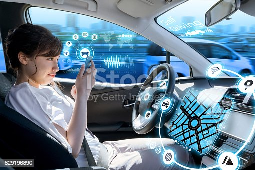829192098 istock photo young woman using a smart phone in a autonomous car. driverless car. self driving vehicle. heads up display. automotive technology. 829196890