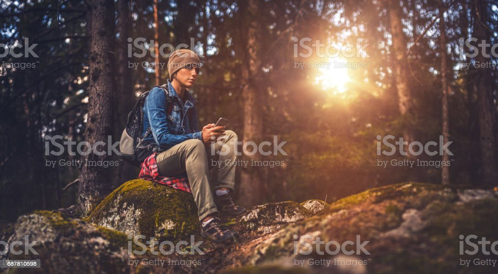 Young woman using a smartphone in the forest stock photo