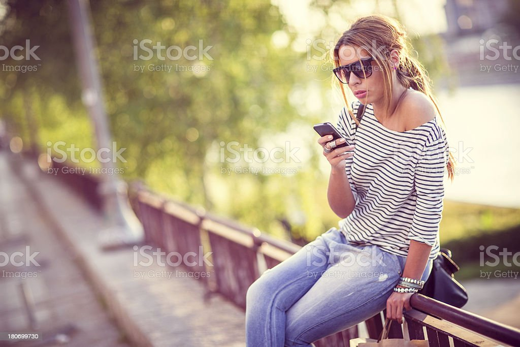Young woman using a smartphone outdoors royalty-free stock photo