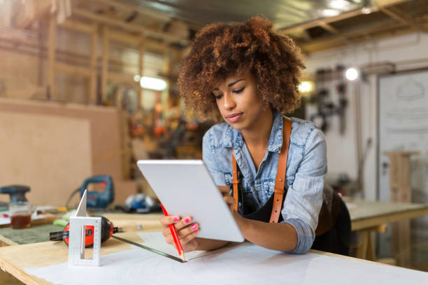 young woman using a tablet in her workshop - owner stock pictures, royalty-free photos & images