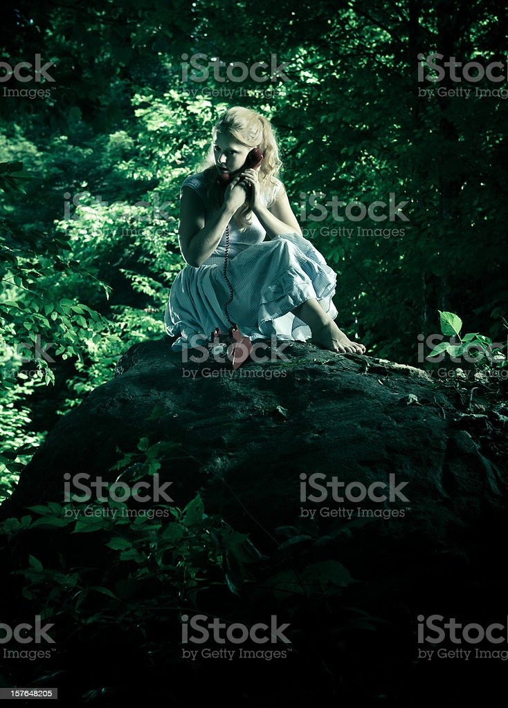 young woman using a vintage phone in the forest stock photo