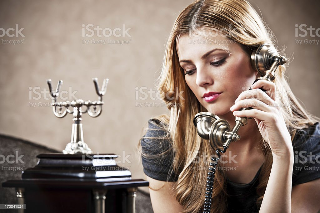 Young woman using an antique phone. stock photo