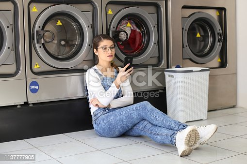 istock Young woman using an app at a laundromat 1137777905