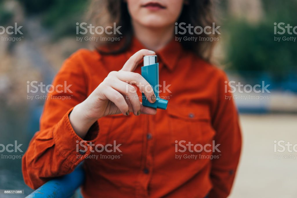 Young woman using an asthma inhaler outdoors stock photo