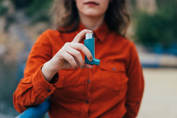 Young woman using an asthma inhaler outdoors Young woman using an asthma inhaler outdoors military attack stock pictures, royalty-free photos & images