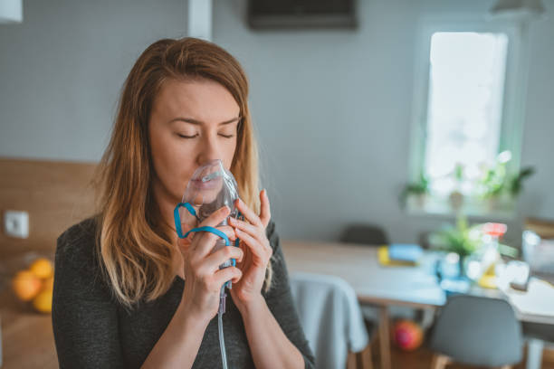 ung kvinna som använder en astma inhalator - andningssystem bildbanksfoton och bilder