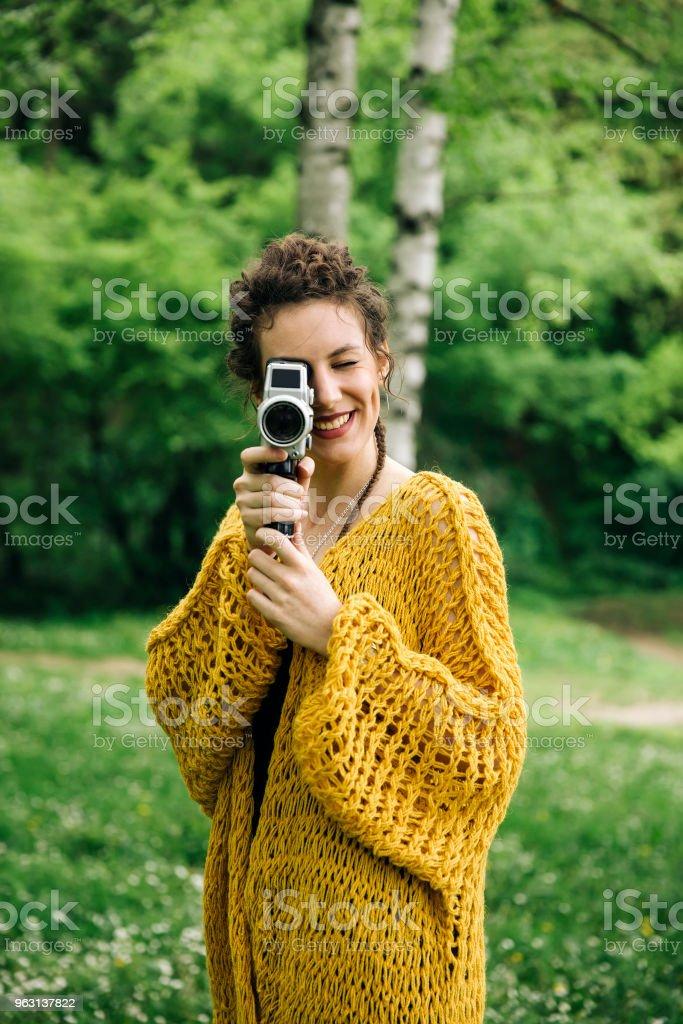 Ung kvinna med en vintage film kamera i en park - Royaltyfri Endast vuxna Bildbanksbilder