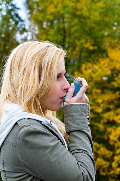 Young Woman Using As Asthma Inhaler Outdoors stock photo