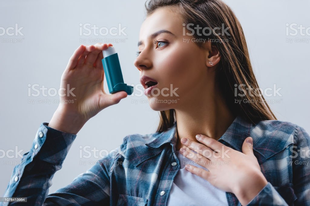 young woman using asthma inhaler and looking away isolated on grey stock photo