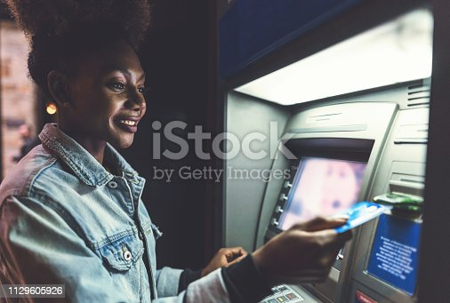 Cheerful African-American woman using her bank card at the ATM in the evening