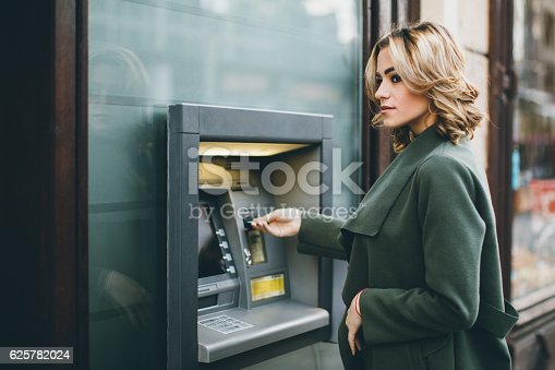 istock Young woman using ATM 625782024