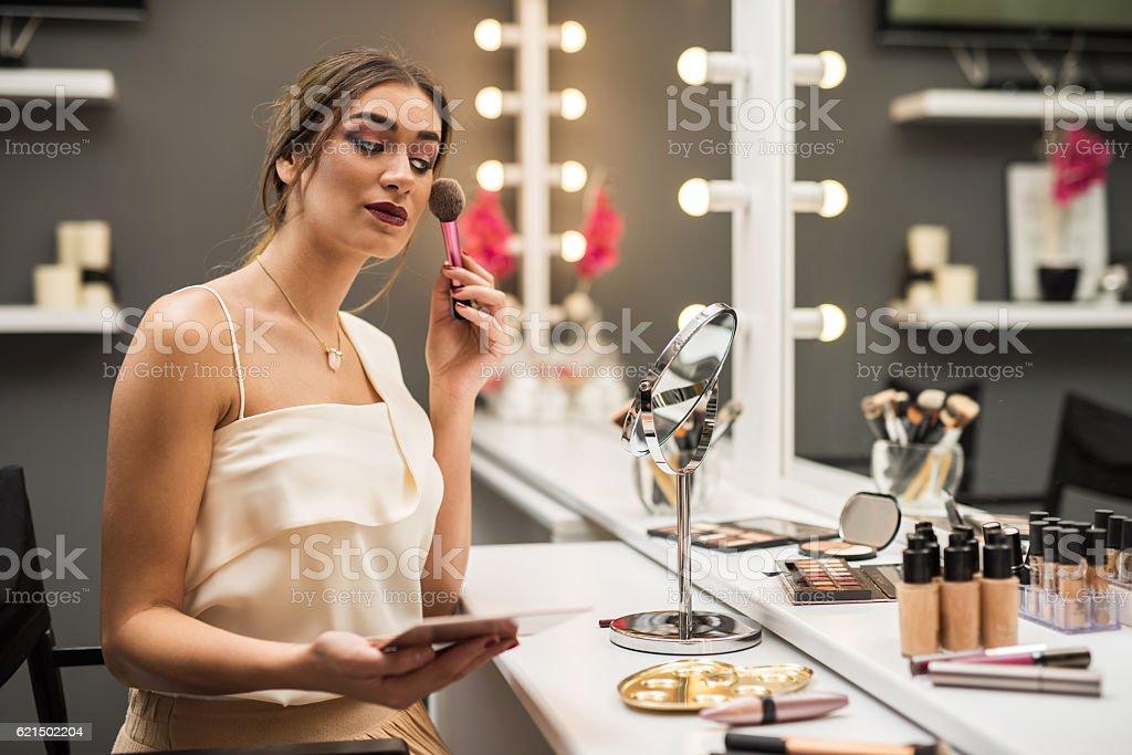 Young woman using blush brush in make-up studio. foto stock royalty-free