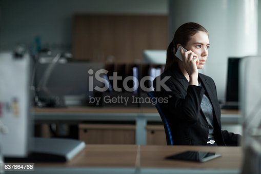 istock Young woman using cell phone in business office 637864768