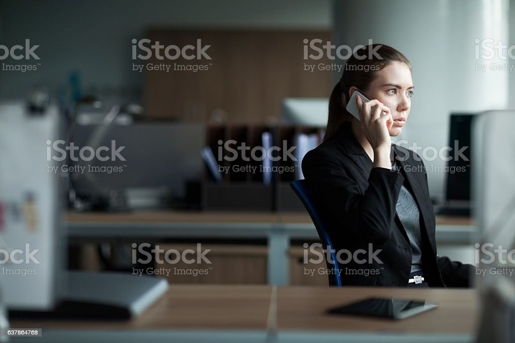 Young woman using cell phone in business office stock photo