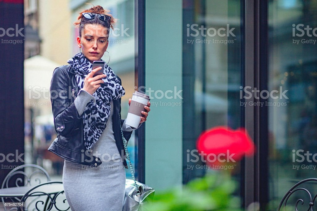 Jeune femme à l'aide de téléphone portable dans la rue photo libre de droits