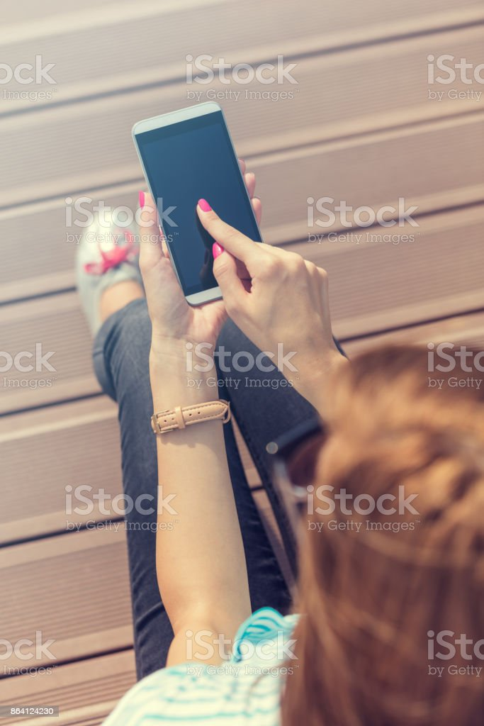 Young woman using cellphone while sitting on the stairs. royalty-free stock photo