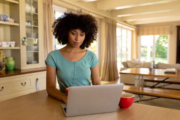 Young woman using computer in the kitchen stock photo