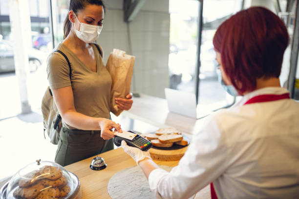 Young woman using contact less payment in bakery during Corona virus stock photo