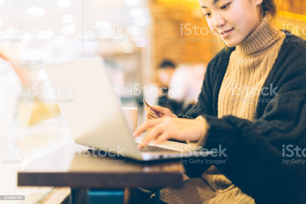 young woman using credit card and laptop in cafe stock photo