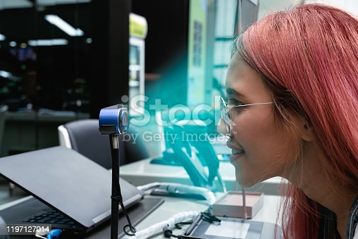 istock Young woman using digital biometric identification facial scanner to authorise cashless payment at retail store 1197127014