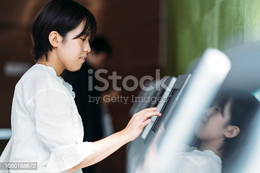 A young woman is using a digital electronic check in device at a counter.