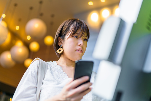 Young woman using digital device at counter