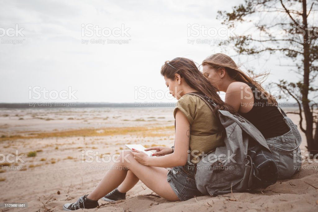 Young woman using digital tablet by friend on sand Young woman using digital tablet by friend in desert. Female explorers are sitting on sand. Hipsters are spending summer vacation together. 20-24 Years Stock Photo