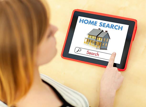junge frau mit digitalen tablet-computer zur wohnungssuche - immobilienangebote stock-fotos und bilder