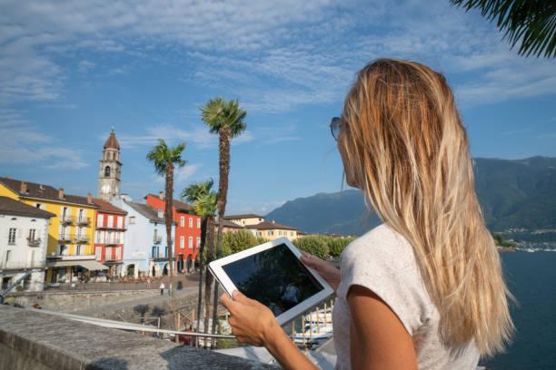 Junge Frau mit digital-Tablette in kleinen Schweizer Dorf in der Nähe von See und Bergen – Foto