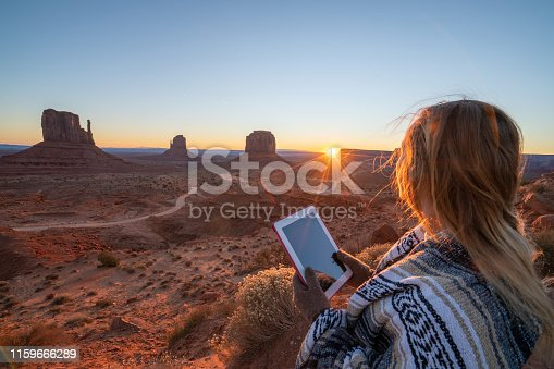 istock Young woman using digital tablet in the American desert; Monument valley USA; People travel planning vacations concept 1159666289