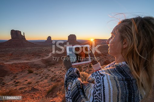 istock Young woman using digital tablet in the American desert; Monument valley USA; People travel planning vacations concept 1159666327