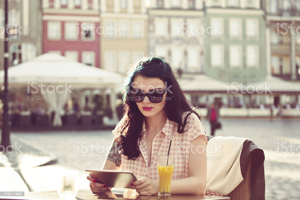 Young woman using digital tablet in the outdoor restaurant Young hipster woman with tatoo on her arm wearing sunglasses sitting at the table in outdoor restaurant in the city and using a digital tablet. Orange juice on the table. Summer time.  2015 Stock Photo