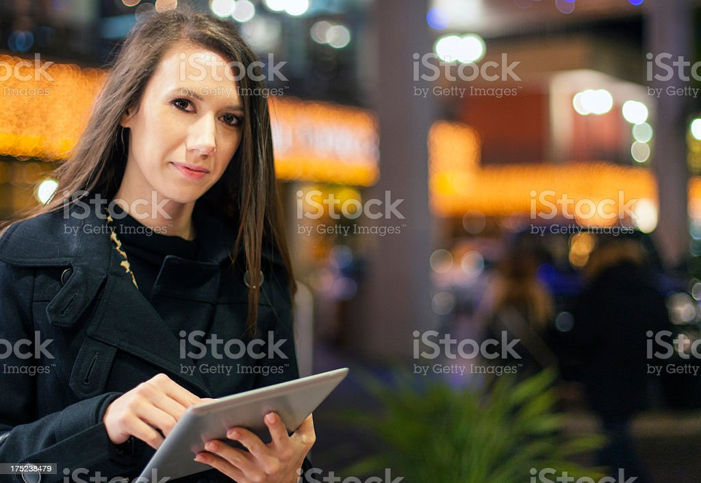 Young woman using digital tablet on city street royalty-free stock photo