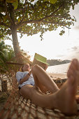Young woman using her digital tablet on an hammock in a tropical scenery during sunset time.