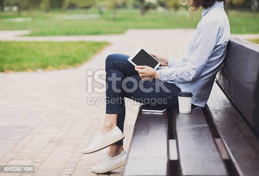 istock Young woman using digital tablet outdoors 645387496