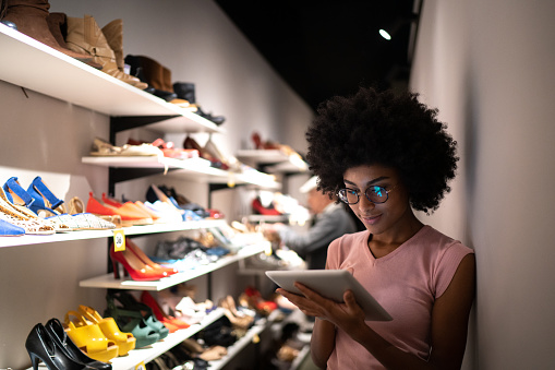Young woman using digital tablet to check invetory at a shoe store