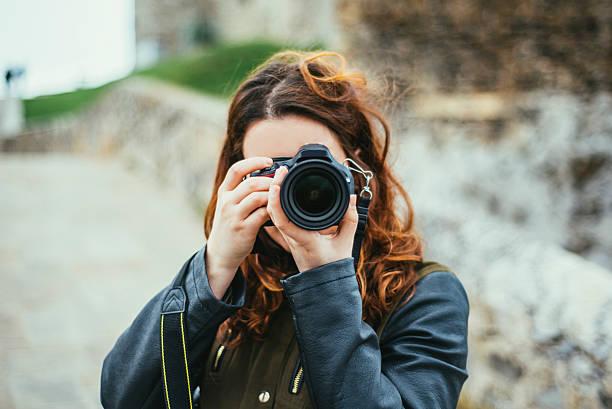young woman using dslr camera - spiegelreflexcamera stockfoto's en -beelden